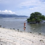 Kenna doing a yoga move on the beach of Gili Travagan.