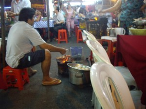 A guy roasting live prawns, shortly before one of them hopped right off the grill
