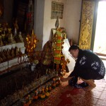 Scott setting down an offering at the Buddhist temple on the hilltop in Luang Prabang