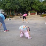 A little 2-yr old girl doing aerobics in the park
